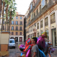 man with balloons in plaza